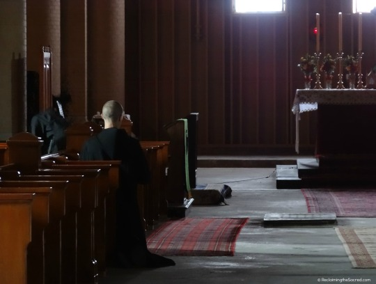 A monk prays alone in choir, before the altar and under the light.