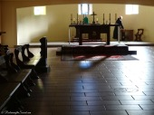 A monk goes about his daily work in the background of the lower church, while sunlight streams in through the windows.